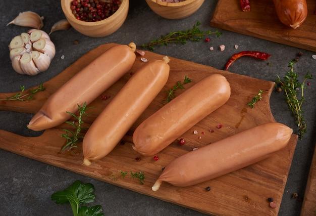 Świeże surowe kiełbasy i składniki do gotowania. klasyczne kiełbaski wieprzowe gotowane na desce do krojenia z papryką, rozmarynem, ziołami i przyprawami.