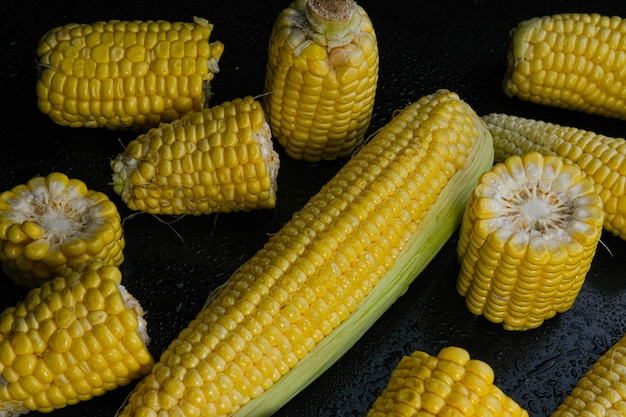 Świeże surowe kolby kukurydzy cukrowej na czarnym tle. zbliżenie.