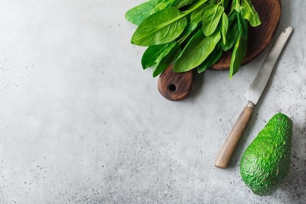 Świeże, surowe liście szpinaku na drewnianym rustykalnym stojaku na szarym tle starego betonu. składniki na sałatkę.