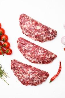 Świeże surowe mielone domowe rolnicy grillowe hamburgery wołowe zestaw, na białym tle kamiennego stołu, widok z góry płaski lay