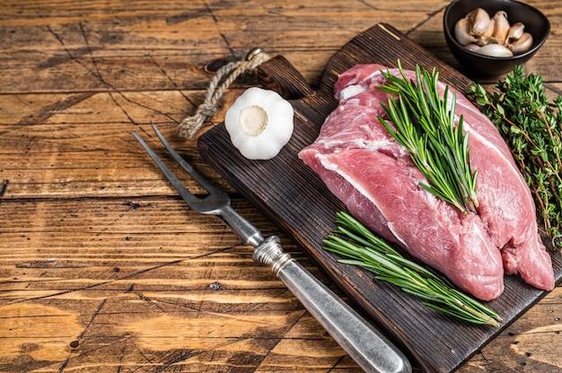 Świeże surowe mięso łopatki wieprzowej ze składnikami i przyprawami na pokładzie drewnianego rzeźnika. drewniane tła. widok z góry. skopiuj miejsce.
