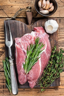 Świeże surowe mięso łopatki wieprzowej ze składnikami i przyprawami na pokładzie drewnianego rzeźnika. drewniane tła. widok z góry.