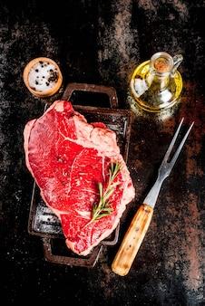 Świeże surowe mięso, marmurowy stek wołowy z marmuru na desce do grillowania, ze składnikami do gotowania. na ciemnym zardzewiałym metalowym stole, widok z góry copyspace