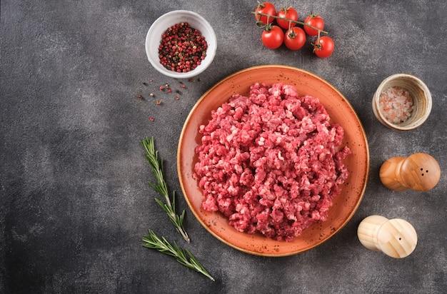 Świeże surowe mięso mielone, mielona wołowina, mięso mielone z ziołami i przyprawami na talerzu, widok z góry.