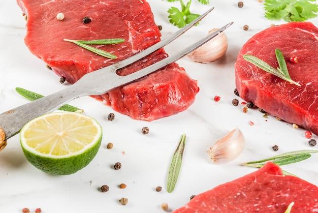 Świeże surowe mięso. polędwica wołowa, steki z ziołami i przyprawami do gotowania