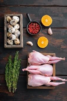 Świeże surowe mięso przepiórcze z ziołami, leżak na płasko, na ciemnym drewnianym stole