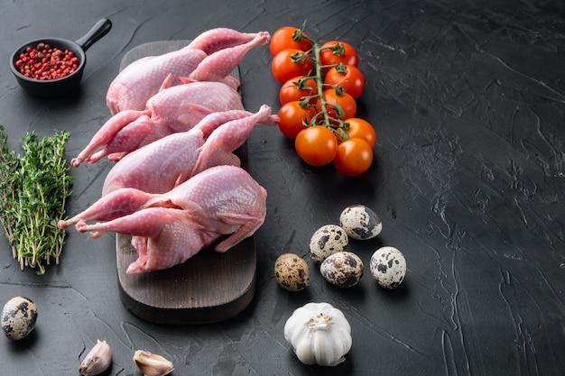Świeże surowe mięso przepiórki gotowe do gotowania, na czarnym stole