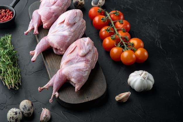 Świeże surowe mięso przepiórki z ziołami, na czarnym stole