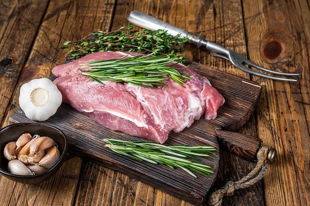 Świeże surowe mięso wieprzowe łopatki z dodatkami i przyprawami na drewnianej desce rzeźnika