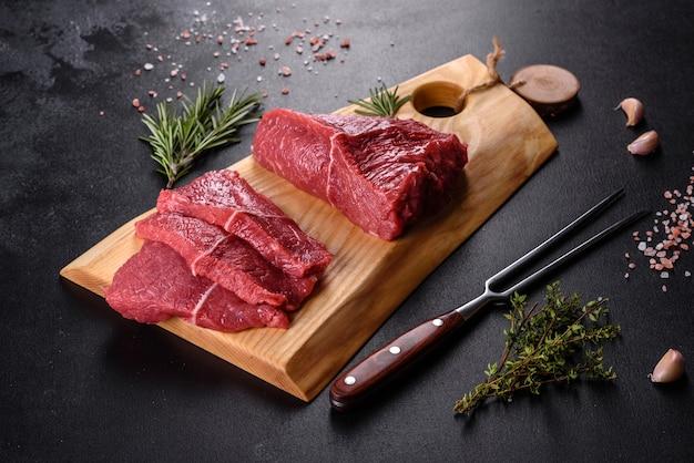 Świeże surowe mięso wołowe do przygotowania pysznego soczystego steku z przyprawami i ziołami. preparat do mięs z grilla