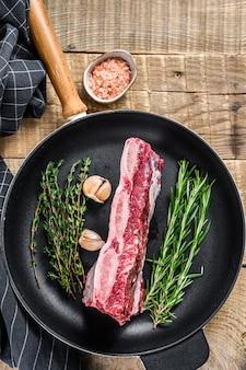 Świeże surowe mięso wołowe krótkie żeberka na patelni z ziołami. drewniane tła. widok z góry.
