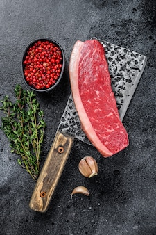 Świeże surowe mięso wołowe z polędwicy wołowej na tasak rzeźnika na drewnianym stole. widok z góry.