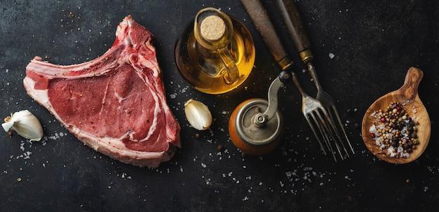 Świeże surowe mięso z przyprawami i solą na ciemnym tle rustykalnym.