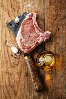 Świeże surowe mięso z przyprawami i solą na drewnianym rustykalnym.
