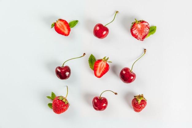 Świeże, surowe organiczne sezonowe owoce i jagody. jednolity wzór, wiśnie, mięta, truskawka na białym. widok z góry copyspace