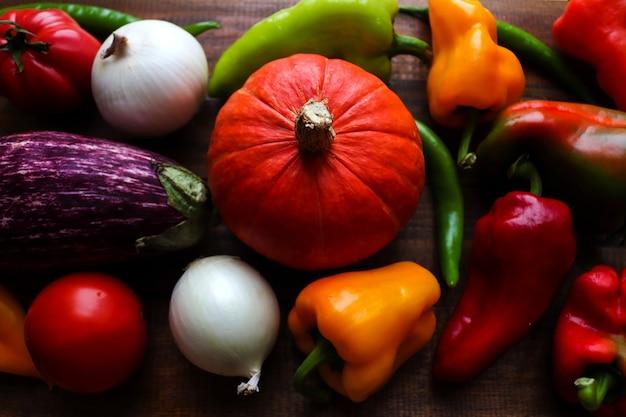 Świeże surowe papryki dyni papryczki chili pomidory cebula i bakłażan tło warzywne