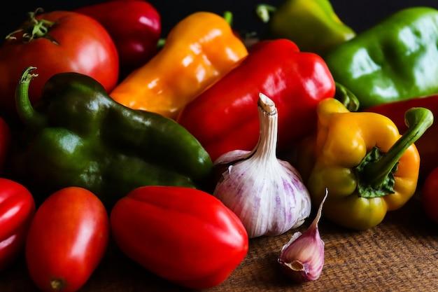 Świeże, surowe papryki, pomidory i czosnek na drewnianym tle koncepcja zbiorów zdrowej żywności detoks