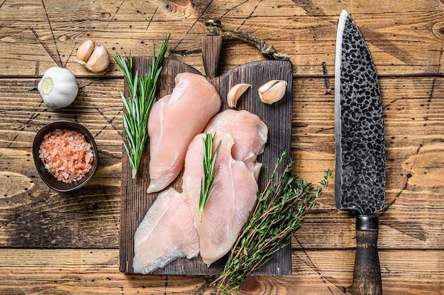 Świeże surowe plastry pokrojonego fileta z piersi kurczaka na drewnianej desce do krojenia z nożem kuchennym