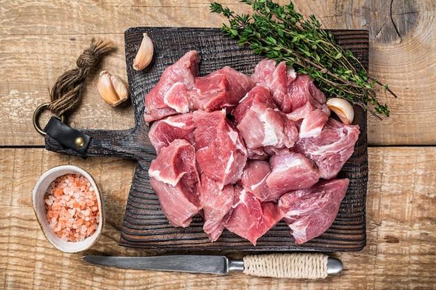 Świeże surowe pokrojone w kostkę mięso młode wieprzowe z przyprawami na drewnianym pokładzie rzeźnika. drewniane tła. widok z góry.