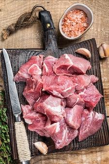 Świeże surowe pokrojone w kostkę mięso młode wieprzowe z przyprawami na pokładzie drewnianej rzeźnika
