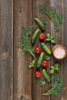 Świeże surowe pomidory, ogórki i sezonowe zielenie. odgórny widok, szorstki plan na rocznika drewnianym stole