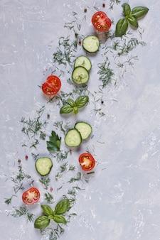 Świeże surowe pomidory, ogórki i sezonowe zielenie. widok z góry, zbliżenie na vintage szary stół
