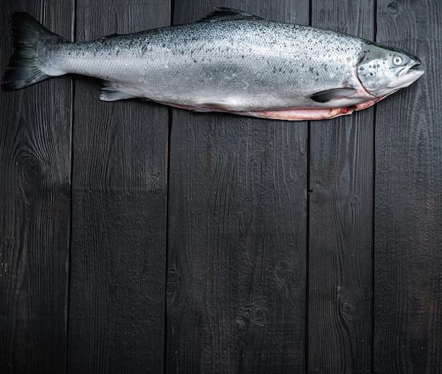 Świeże surowe pstrągi czerwone ryby na czarnej drewnianej powierzchni, płaskie leżały z miejscem na tekst.