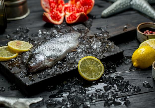Świeże surowe ryby, cytryna, granat i kostki lodu.