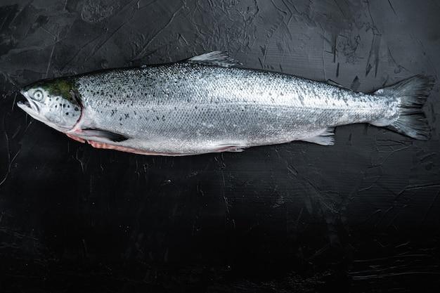 Świeże surowe ryby czerwone łosoś na czarnym tle, widok z góry z miejsca na kopię.
