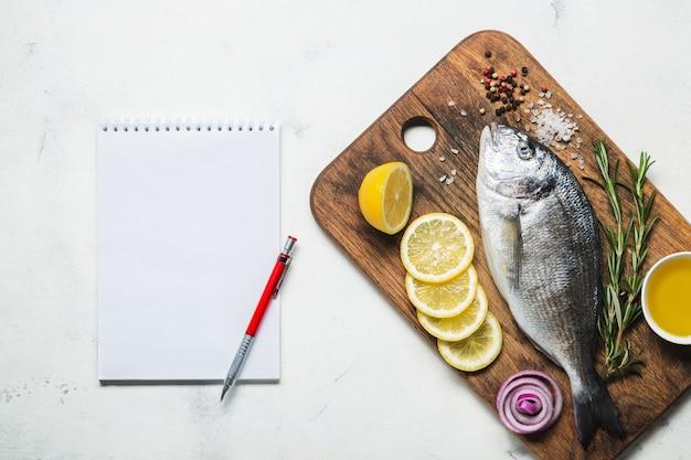 Świeże surowe ryby dorado na rustykalnej drewnianej desce do krojenia z przyprawami i notatnikiem do przepisu lub menu. widok z góry na białym tle.