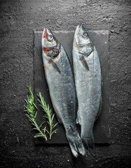 Świeże surowe ryby na kamieniu deska z rozmarynem na czarnym stole rustykalnym