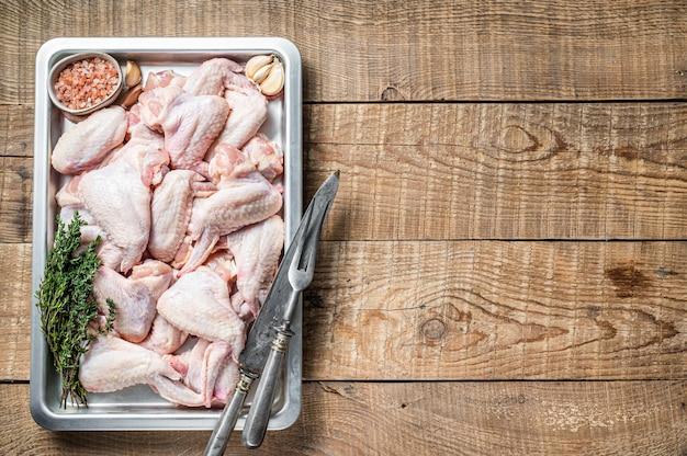 Świeże surowe skrzydełka z kurczaka mięso drobiowe na tacy kuchennej z ziołami. drewniane tło. widok z góry. skopiuj miejsce.