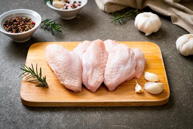 Świeże surowe środkowe skrzydełka z kurczaka na desce ze składnikami