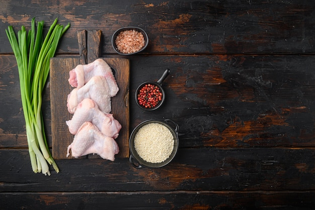 Świeże surowe środkowe skrzydełka z kurczaka z zestawem składników i sezamem, na drewnianej desce do krojenia, na starym ciemnym drewnianym stole, widok z góry na płasko