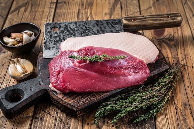 Świeże surowe steki z piersi kaczki na desce rzeźnika z tasakiem do mięsa. drewniany stół. widok z góry.