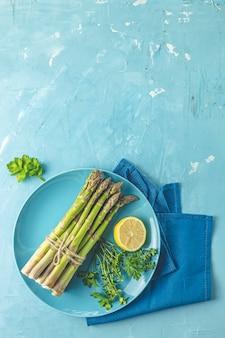 Świeże surowe szparagi z cytryną i pietruszką w niebieskim talerzu ceramicznym z serwetką na jasnoniebieskiej powierzchni stołu betonowego