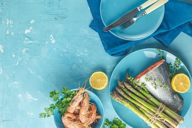 Świeże surowe szparagi z pstrągiem, cytryną i pietruszką, krewetkami, krewetkami w niebieskich ceramicznych talerzach