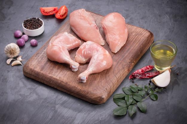 Świeże, surowe udka z kurczaka bez skóry i surowa pierś z kurczaka na brązowej drewnianej podstawie