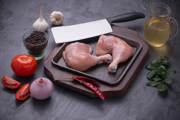 Świeże, surowe udka z kurczaka bez skóryułożone w sizzler z szarym teksturowanym tłem