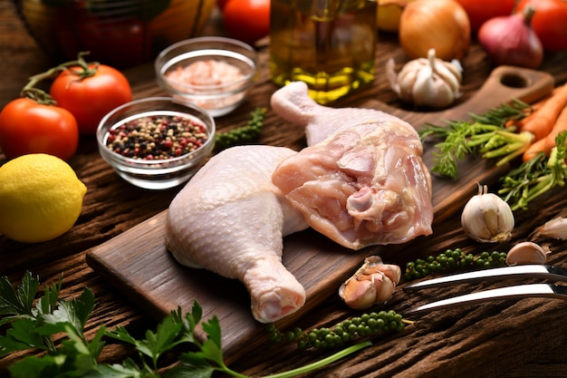 Świeże, surowe udka z kurczaka ze składnikami do gotowania na drewnianej desce do krojenia