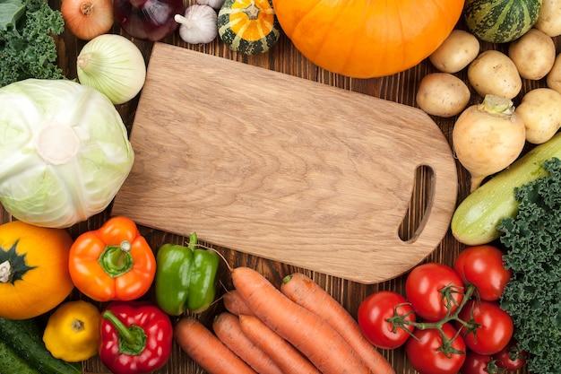 Świeże surowe warzywa i deska do krojenia, widok z góry