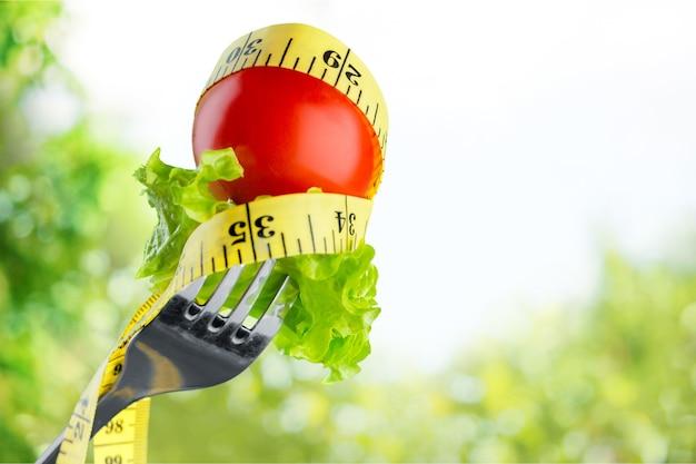 Świeże surowe warzywa na widelcu i taśma miernicza na tle