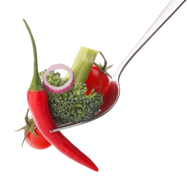Świeże surowe warzywa na widelec na białym tle na białe tło wyłącznik. koncepcja zdrowego odżywiania.