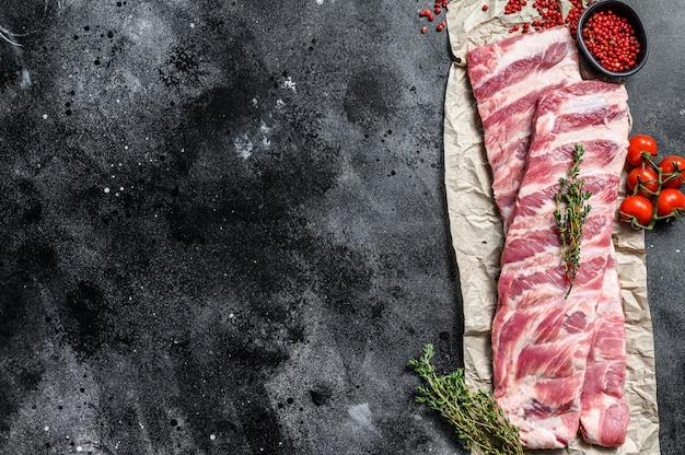 Świeże surowe żeberka wieprzowe z przyprawami i ziołami.