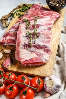 Świeże surowe żeberka wieprzowe z rozmarynem, pieprzem i czosnkiem.