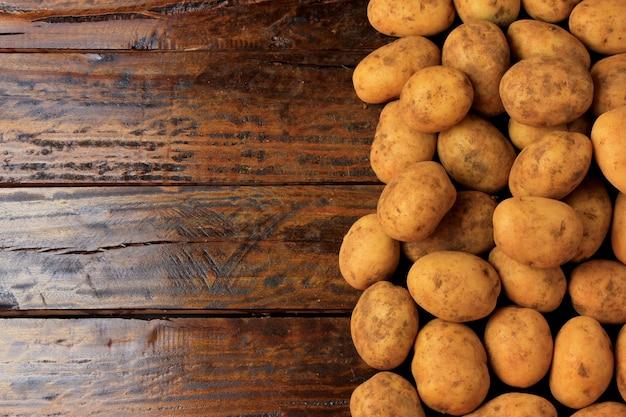 Świeże surowe ziemniaki ułożone na boku drewnianego stołu z wolnym miejscem na tekst