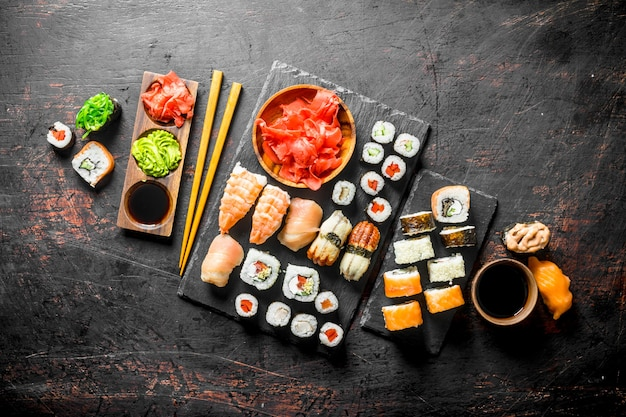 Świeże sushi rolki na czarnym kamieniu stoją na czarnym rustykalnym stole