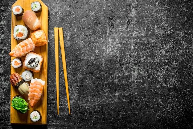 Świeże sushi rolki na drewnianej desce do krojenia z pałeczkami. na ciemnym rustykalnym stole