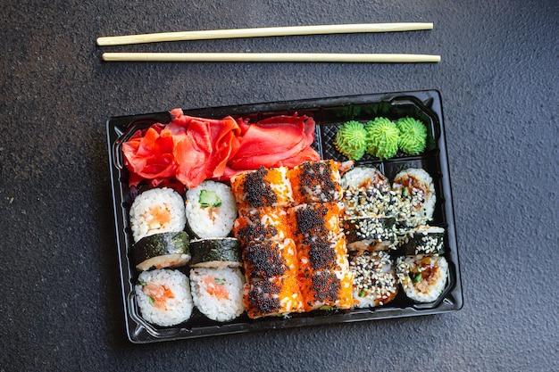 Świeże sushi rolki ryżu łososia, ryżu i nori na stole