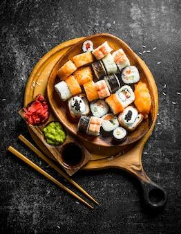 Świeże sushi rolki w talerzu na deska do krojenia z pałeczkami i sosami. na ciemny rustykalny